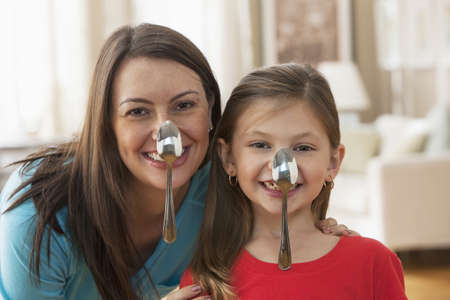 Caucasian mother and daughter balancing spoons on noses LANG_EVOIMAGES