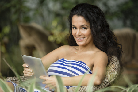 Hispanic woman using tablet computer LANG_EVOIMAGES