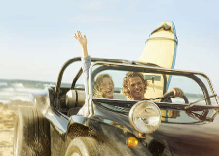 Caucasian couple driving jeep on beach LANG_EVOIMAGES