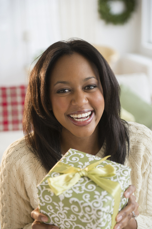 African American woman holding Christmas present LANG_EVOIMAGES