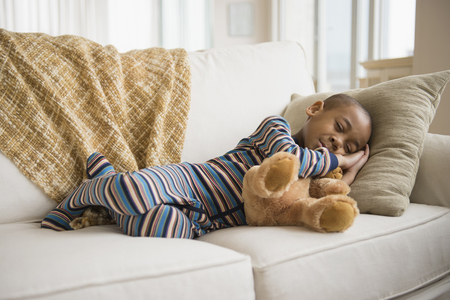 African American boy napping on sofa