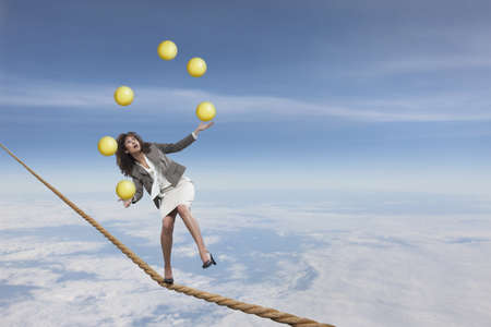 Mixed race businesswoman juggling on tightrope LANG_EVOIMAGES