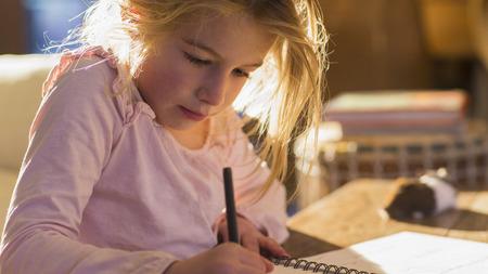Caucasian girl doing homework on desk
