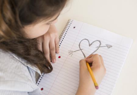 Hispanic girl doodling heart and arrow LANG_EVOIMAGES