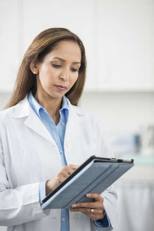 Middle Eastern doctor using tablet computer in office