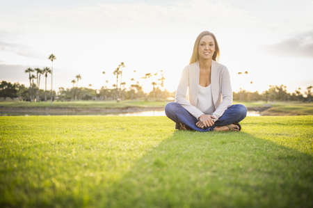 Smiling woman sitting in grass