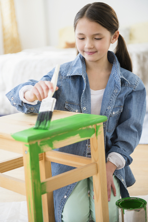 Mixed race girl painting stool LANG_EVOIMAGES