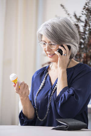 Caucasian woman discussing medication on cell phone LANG_EVOIMAGES