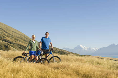 Caucasian couple with bicycles in rural landscape LANG_EVOIMAGES