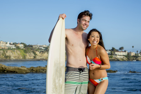 Couple with surfboard smiling together on beach