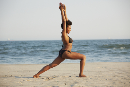 Black woman practicing yoga on beach