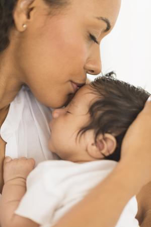 Hispanic mother kissing infant son