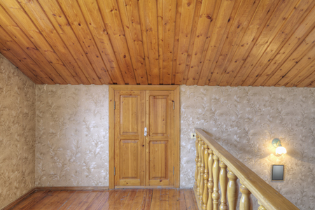 Wooden door and banister with slanted ceiling