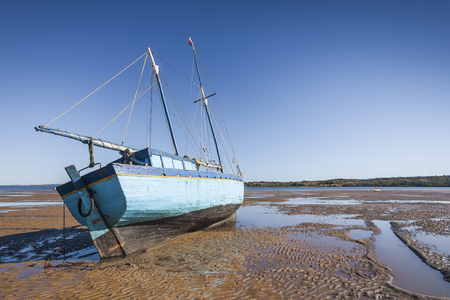 A traditional wooden boat beached at low tide on the sand