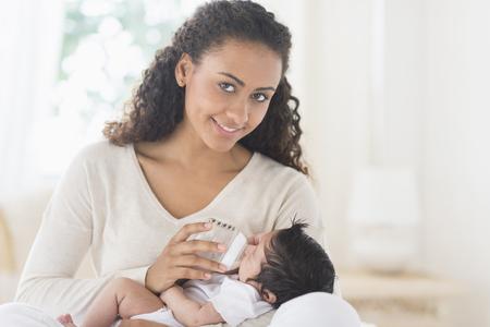 Hispanic mother bottle feeding infant son LANG_EVOIMAGES