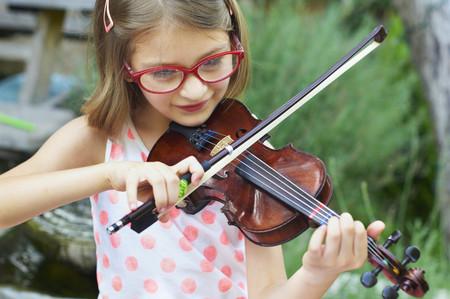 Hispanic girl playing violin outdoors