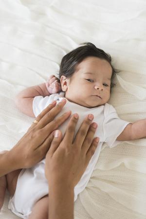 Hispanic mother cradling baby