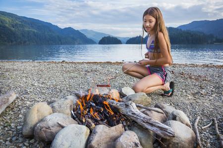 Mixed race girl roasting hot dog at campfire