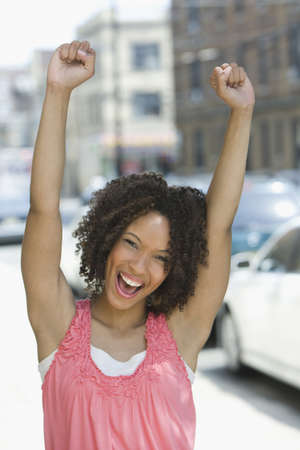 Black woman cheering outdoors
