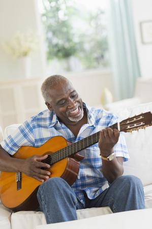Black man playing guitar on sofa