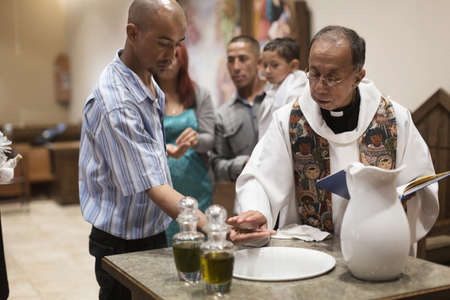 Priest and man performing baptismal rites in church
