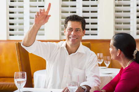 Couple calling waiter at restaurant