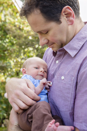 Father holding newborn son outdoors