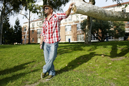 Man leaning against tree branch in park