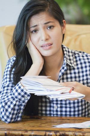 Woman sorting through bills on sofa LANG_EVOIMAGES