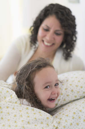 Mixed race mother putting daughter to bed