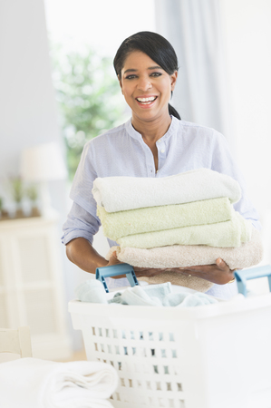 Black woman folding laundry LANG_EVOIMAGES