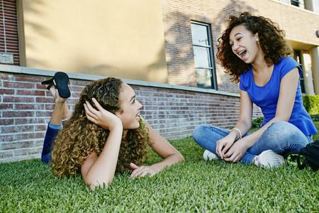 Smíšené rasy dívky mluví v trávě