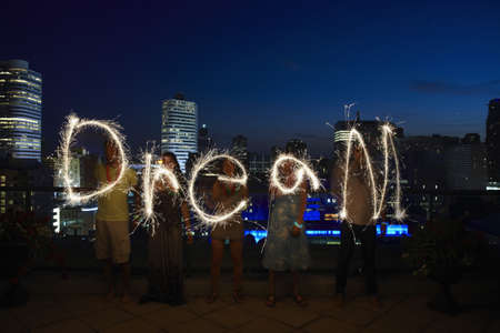 Friends writing dream with sparklers on urban rooftop