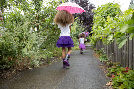 Mixed race girls carrying umbrellas outdoors LANG_EVOIMAGES