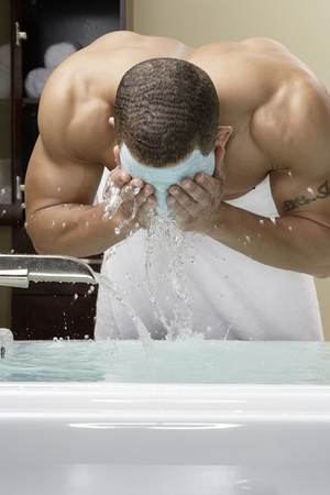 Mixed race man washing off facial mask in bath LANG_EVOIMAGES