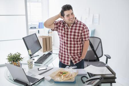 Mixed race businessman smiling at desk LANG_EVOIMAGES