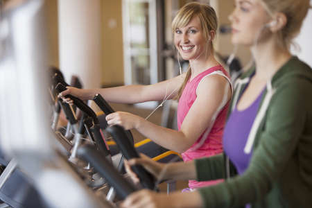 Caucasian women exercising on elliptical trainers in gym