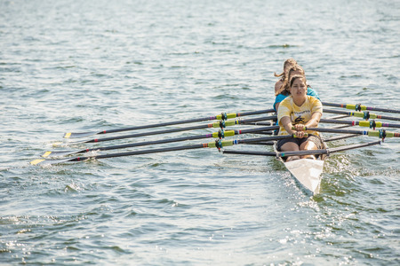 Teenagers rowing together on lake LANG_EVOIMAGES