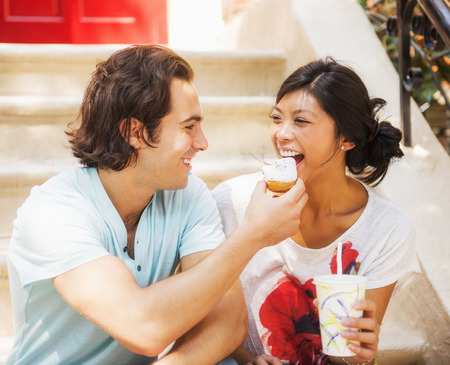 Man feeding donut to girlfriend on front stoop