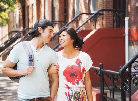 Couple walking on urban sidewalk outside brownstones LANG_EVOIMAGES