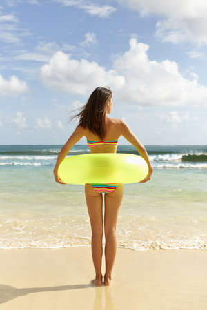 Japanese woman with inflatable ring on beach LANG_EVOIMAGES