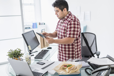 Mixed race businessman working at desk LANG_EVOIMAGES