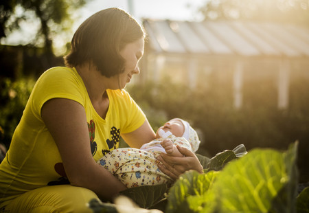 Caucasian mother holding baby girl in garden