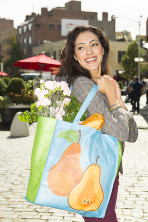 Mixed race woman with shopping bag on city street LANG_EVOIMAGES