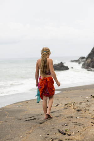 Caucasian girl walking on tropical beach LANG_EVOIMAGES