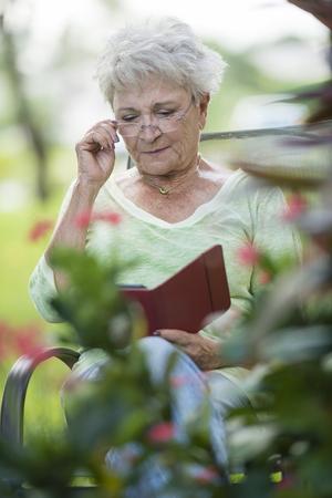 Senior Caucasian woman using digital tablet outdoors LANG_EVOIMAGES