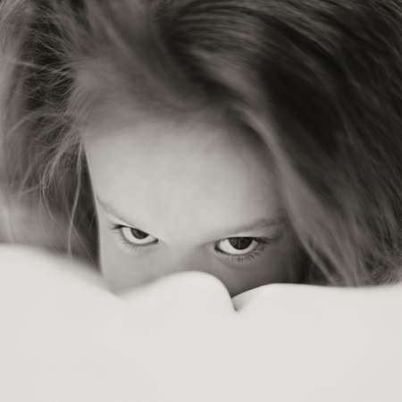 Caucasian girl peering over bed covers LANG_EVOIMAGES