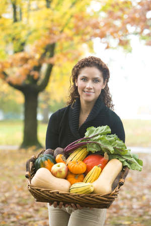 Hispanic woman carrying basket of vegetables outdoors