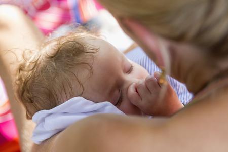 Caucasian mother cradling baby