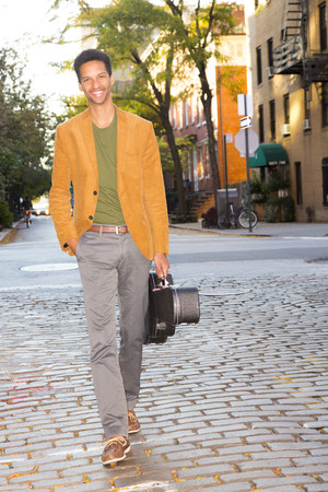 Mixed race man carrying guitar on city street LANG_EVOIMAGES